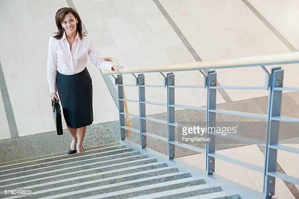 businesswoman climbing a stairway - stairs stock photos and pictures