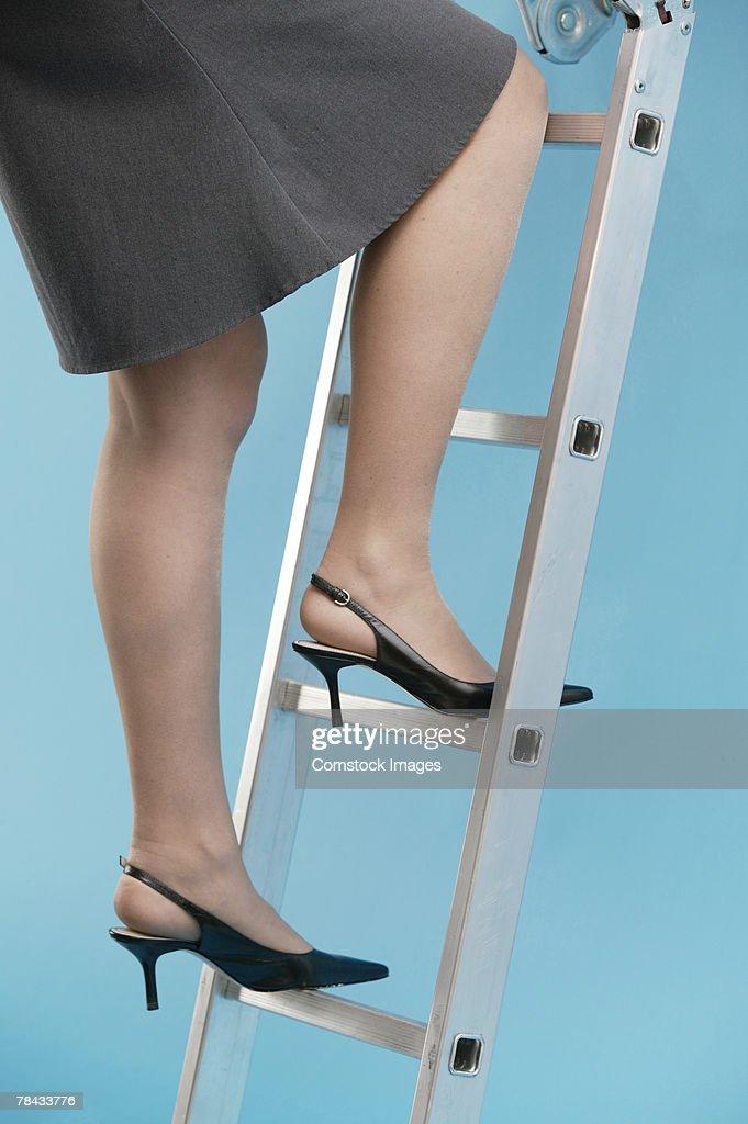 Businesswoman climbing ladder : Stockfoto