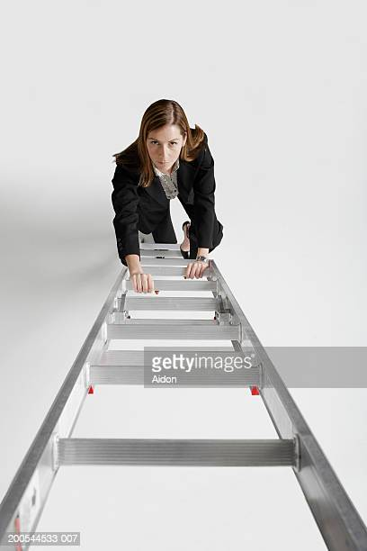 Businesswoman climbing ladder, studio shot