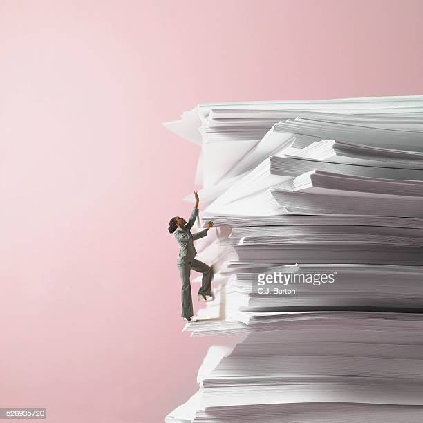 Businesswoman climbing stack of documents