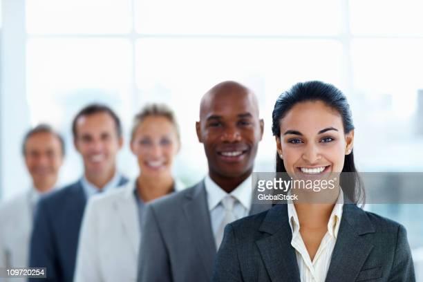 Femme d'affaires avec des collègues debout dans une ligne de sourire
