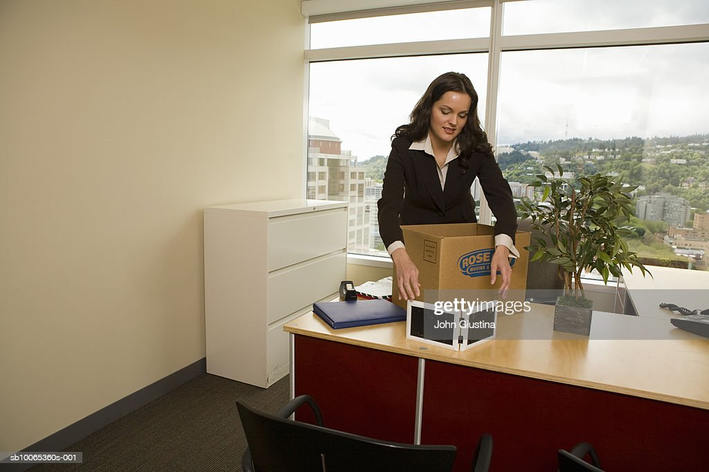 Businesswoman collecting office supply in cardboard box, smiling : Foto stock