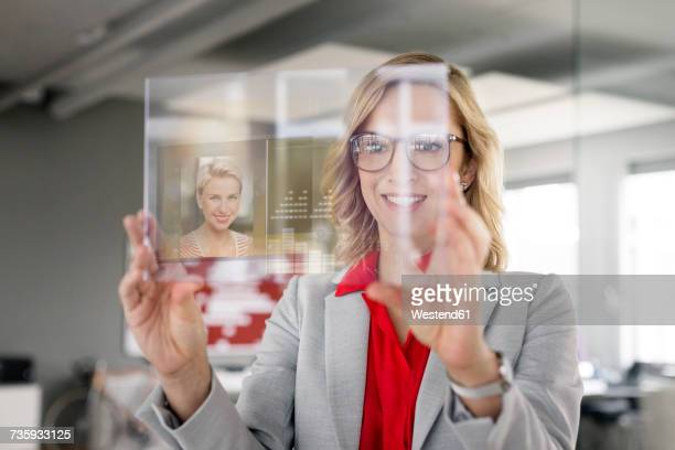 Businesswoman communicating via futuristic portable device