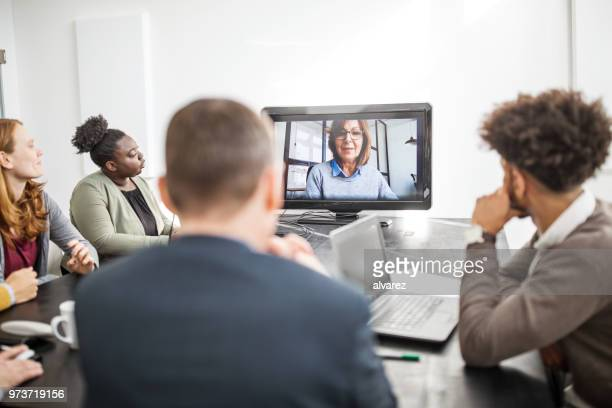 businesswoman communicating with team on video call - webinar stock photos and pictures
