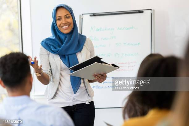 businesswoman conducts employee training class - islam stock pictures, royalty-free photos & images