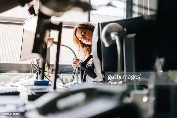 businesswoman connecting computer cables in office - kabel stock-fotos und bilder