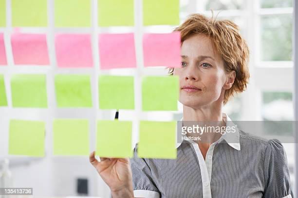 Uma Mulher de Negócios, tendo em conta as linhas de notas adesivas em vidro