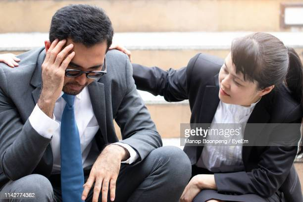 businesswoman consoling businessman while sitting on steps - compassionate eye stock pictures, royalty-free photos & images