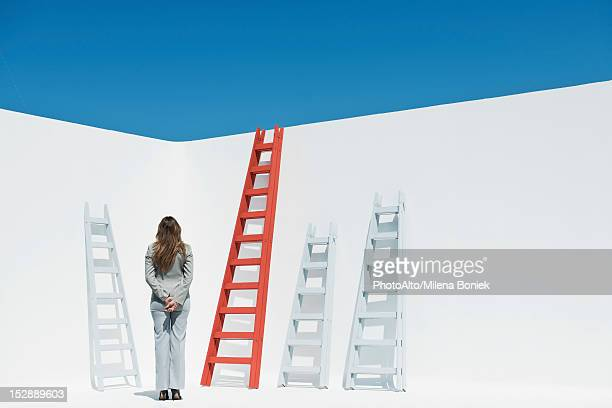 businesswoman contemplating ladders, rear view - ladder of success stock pictures, royalty-free photos & images