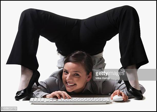 Businesswoman contorting her body while typing