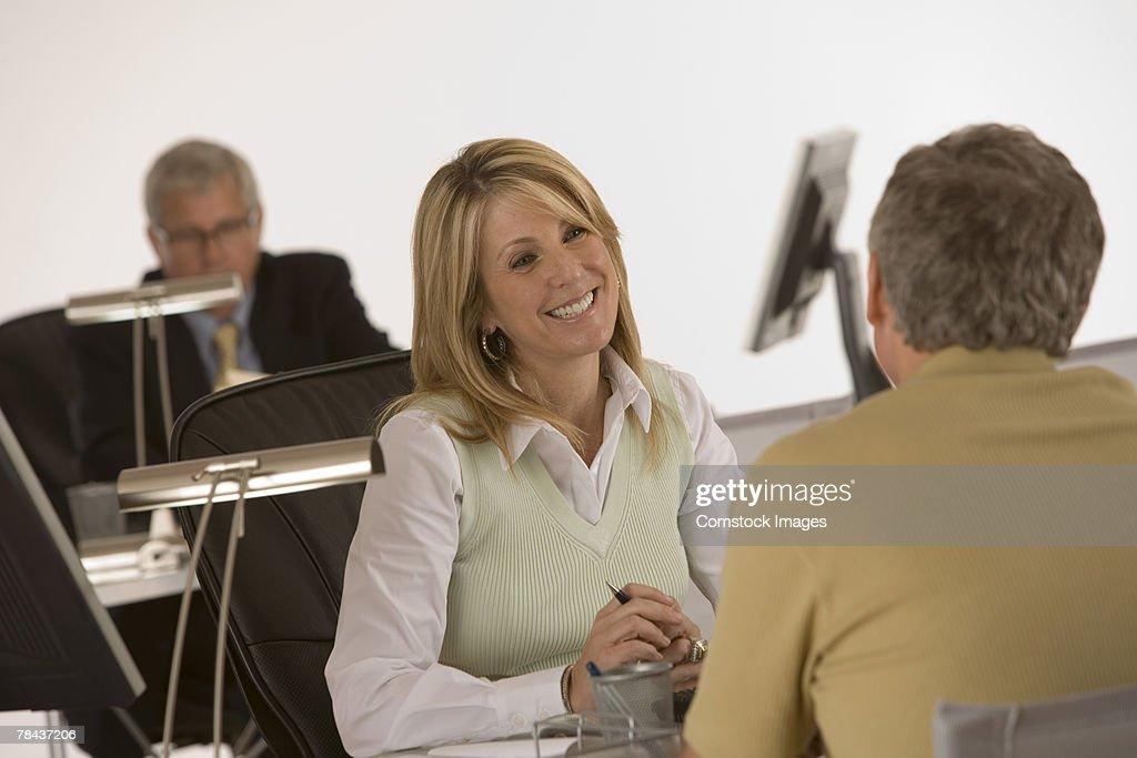 Businesswoman conversing with man : Stockfoto