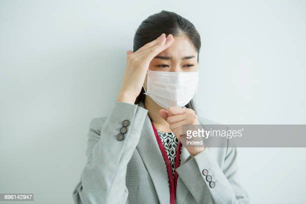 Businesswoman coughing and pressing temple