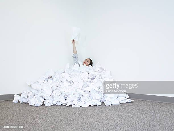 Businesswoman covered in pile of papers holding paper upwards