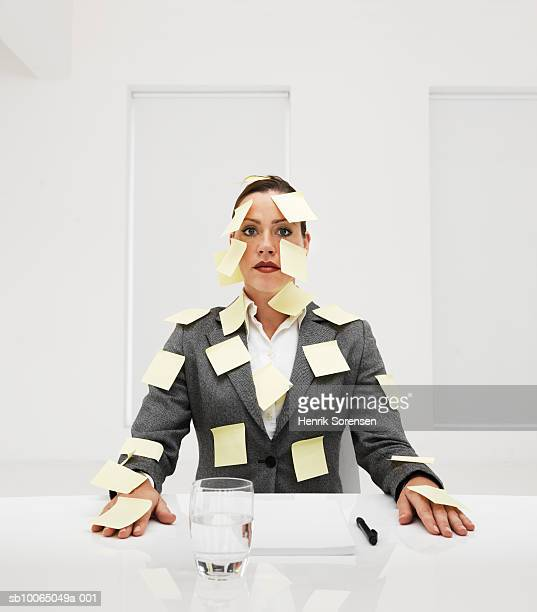 Businesswoman covered with adhesive notes, portrait
