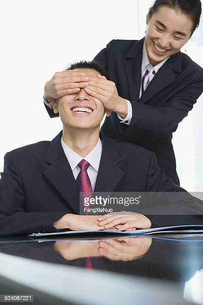 Businesswoman covering businessman's eyes
