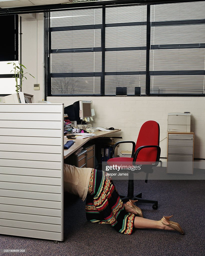 Businesswoman Crawling Under Desk In Office Low Section Side View Stock Photo