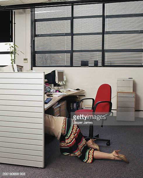 Businesswoman crawling under desk in office, low section, side view