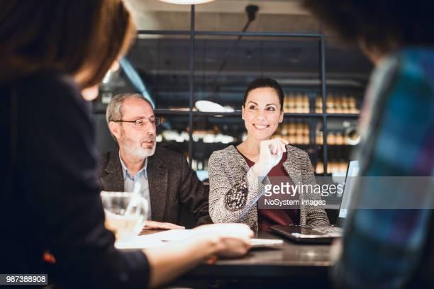 imprenditrice, team leader creativa e il suo team multietnico all'incontro in un ristorante di fascia alta - lunch foto e immagini stock