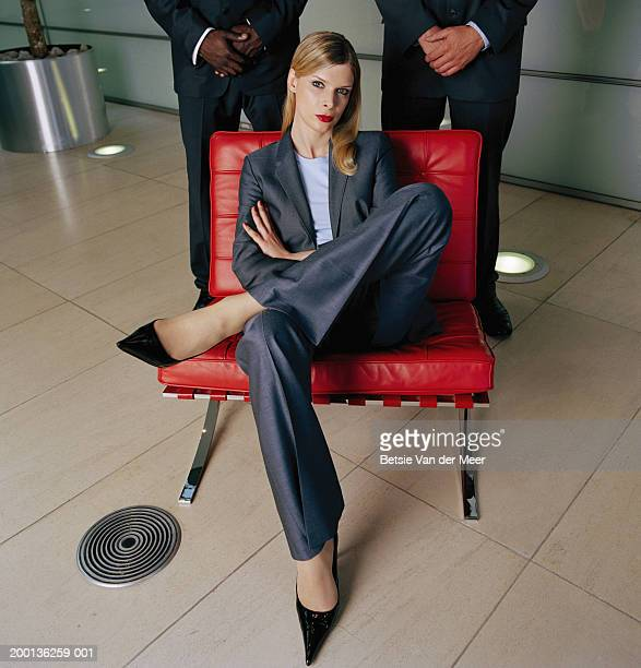 Businesswoman cross legged on chair, portrait, two men in background