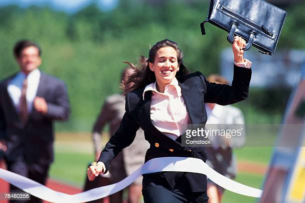Businesswoman crossing finish line of footrace