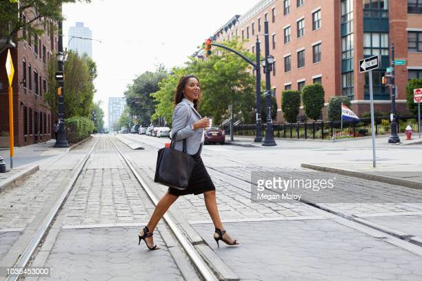 businesswoman crossing light rail tracks - striding stock pictures, royalty-free photos & images
