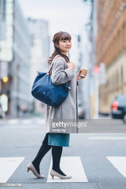 コーヒーを押しながら交差道路で実業家 - 30代 ストックフォトと画像