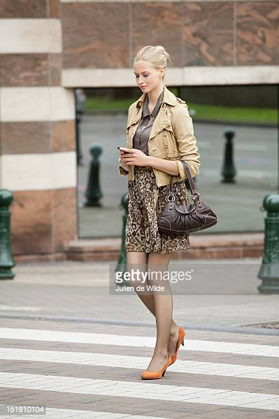 businesswoman crossing the road while using a mobile phone - zebra crossing stock pictures, royalty-free photos & images