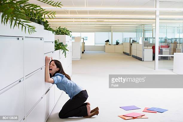 Businesswoman Crying Against File Cabinet