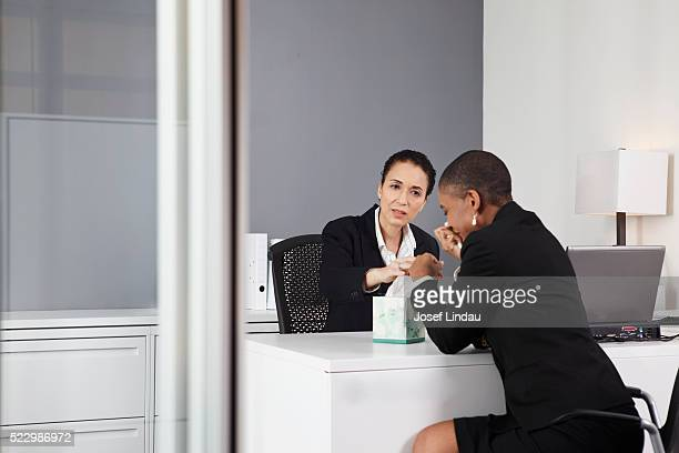 Businesswoman crying in her boss' office