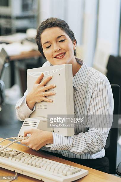 businesswoman cuddling her computer monitor at her desk - chesty love stock pictures, royalty-free photos & images