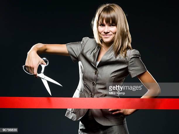 businesswoman cutting a red ribbon - openingsevenement stockfoto's en -beelden