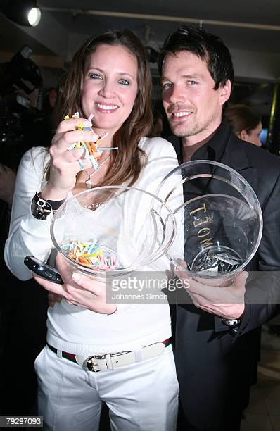 Businesswoman Dana Schweiger and skier Bruno Kernen sell lottery tickets at the club P1 during the ISPO Style Night January 28 2007 in Munich Germany...