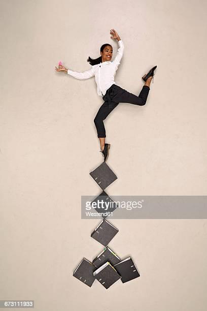 Businesswoman dancing on folders