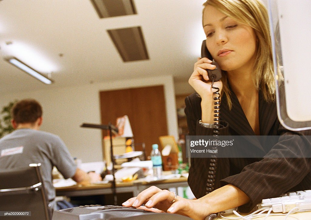 Businesswoman dialing phone in office. : Stockfoto