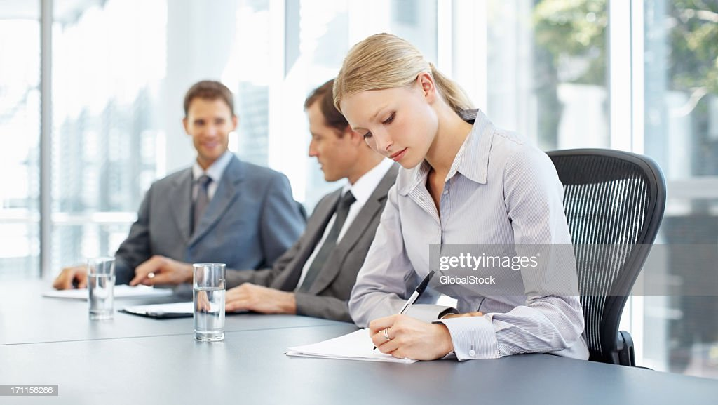 Businesswoman diligently taking notes during a meeting : Stockfoto