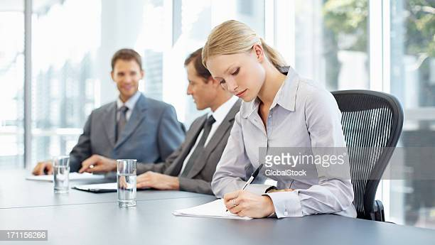 Businesswoman diligently taking notes during a meeting