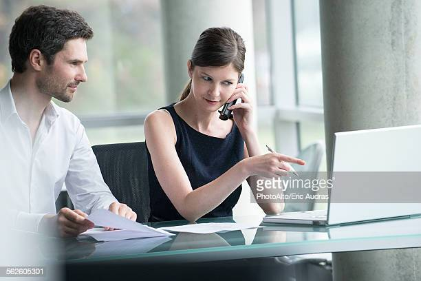 Businesswoman directing colleagues attention to computer screen