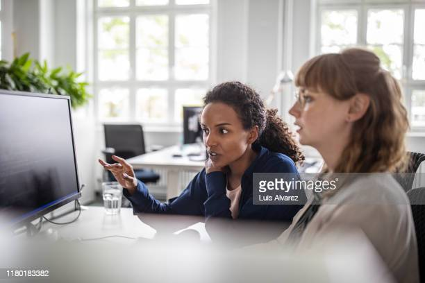 businesswoman discussing coding with coworker in office - data stock pictures, royalty-free photos & images