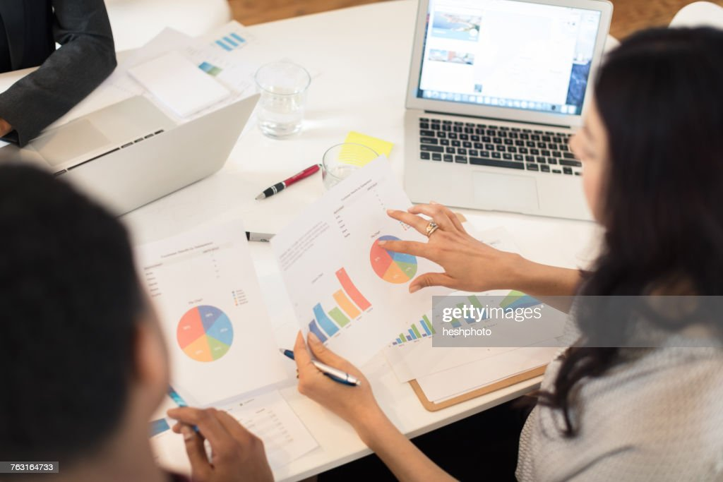 Businesswoman discussing pie charts at conference table meeting : Stock Photo