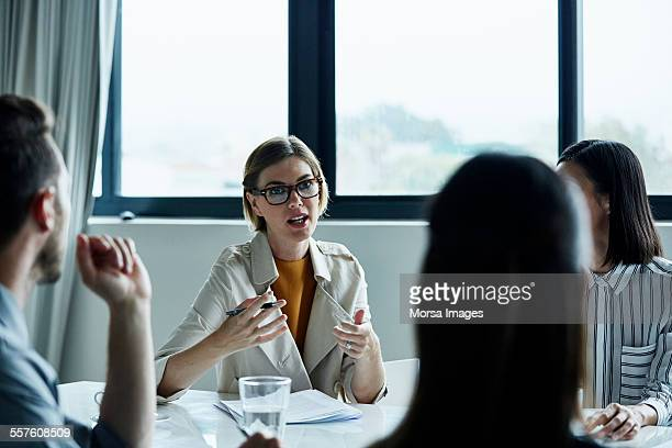 businesswoman discussing plan with colleagues - business plan stock pictures, royalty-free photos & images