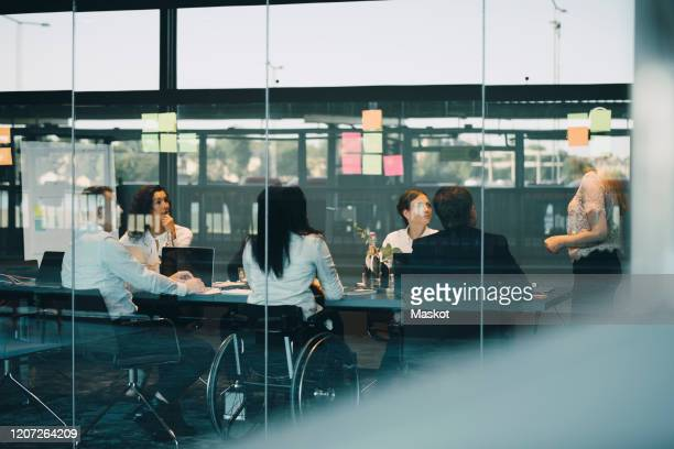 businesswoman discussing strategies with colleagues in office board room - employee engagement stock pictures, royalty-free photos & images