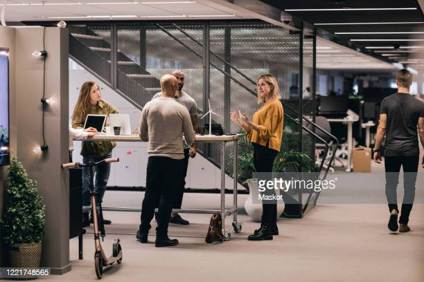 businesswoman discussing strategy with colleagues at office desk - milieukwesties stockfoto's en -beelden