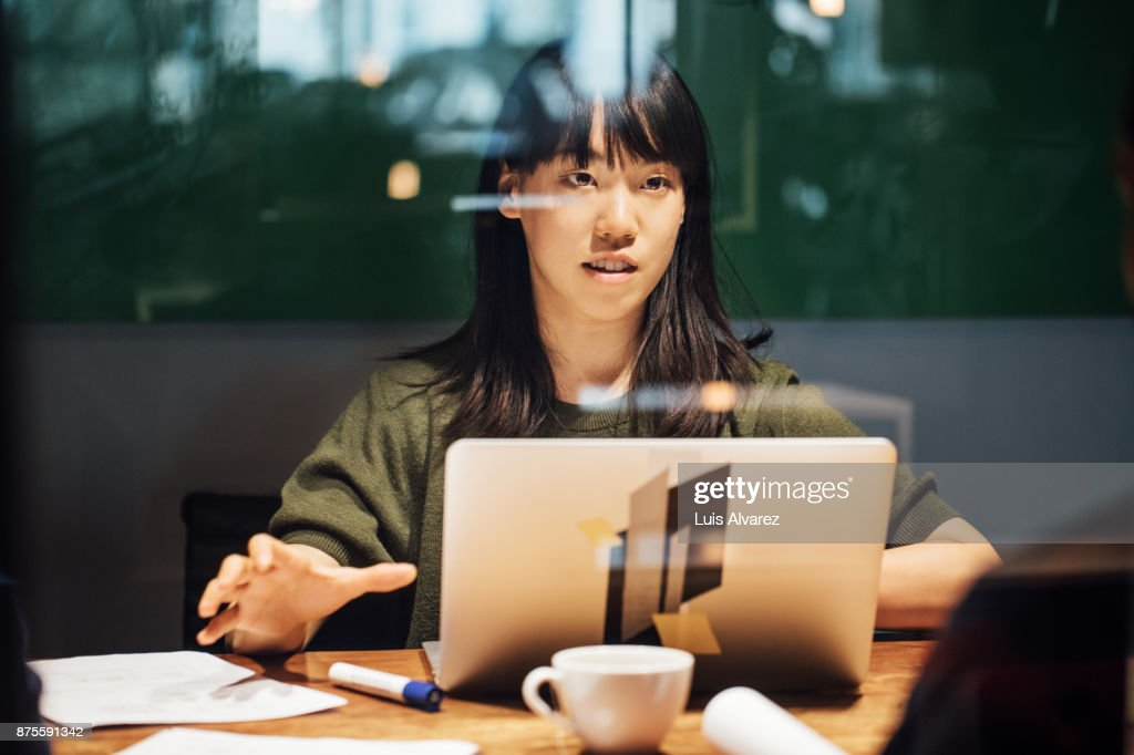 Businesswoman discussing while working late on laptop : Stock-Foto