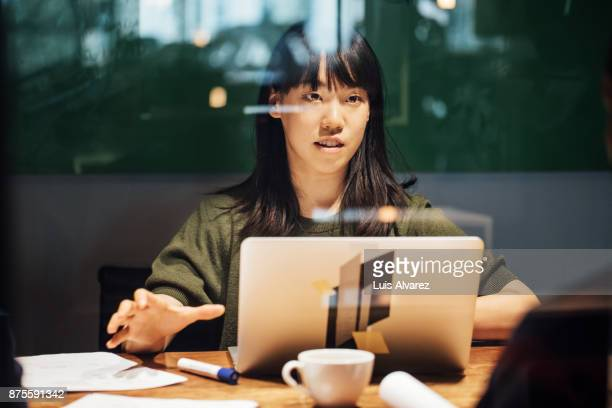 Businesswoman discussing while working late on laptop