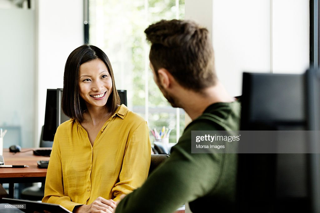 Businesswoman discussing with colleague in office : Stock Photo