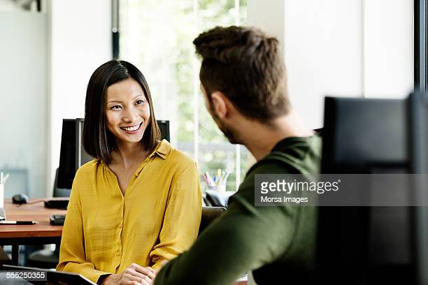 businesswoman discussing with colleague in office - talking stock pictures, royalty-free photos & images