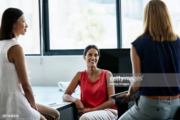 Businesswoman discussing with colleagues at desk