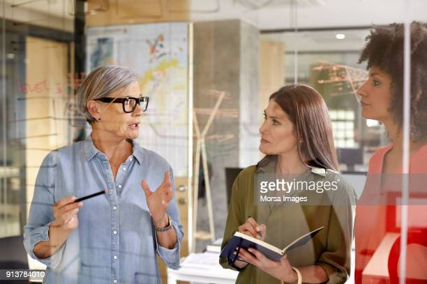 Businesswoman discussing with colleagues at glass