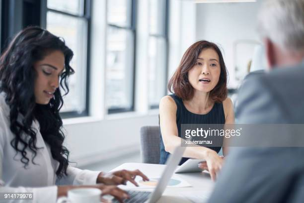 businesswoman discussing with colleagues at table - formal stock pictures, royalty-free photos & images