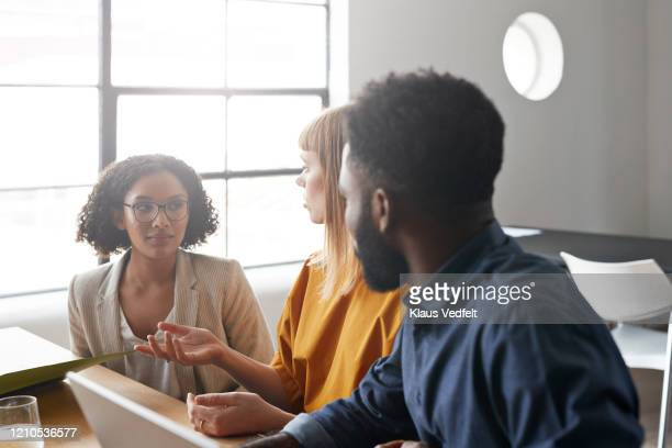businesswoman discussing with colleagues in office - three people stock pictures, royalty-free photos & images